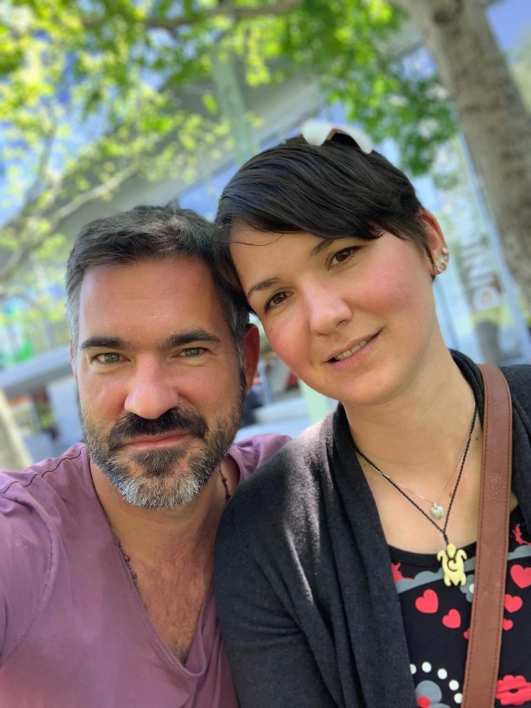 Frank-Christian Marx, a man with short black hair and a full beard has his arms around Karina, a woman with short, brown hair and a flower in her hair. Their heads are leaning against each other and they both smile slightly.