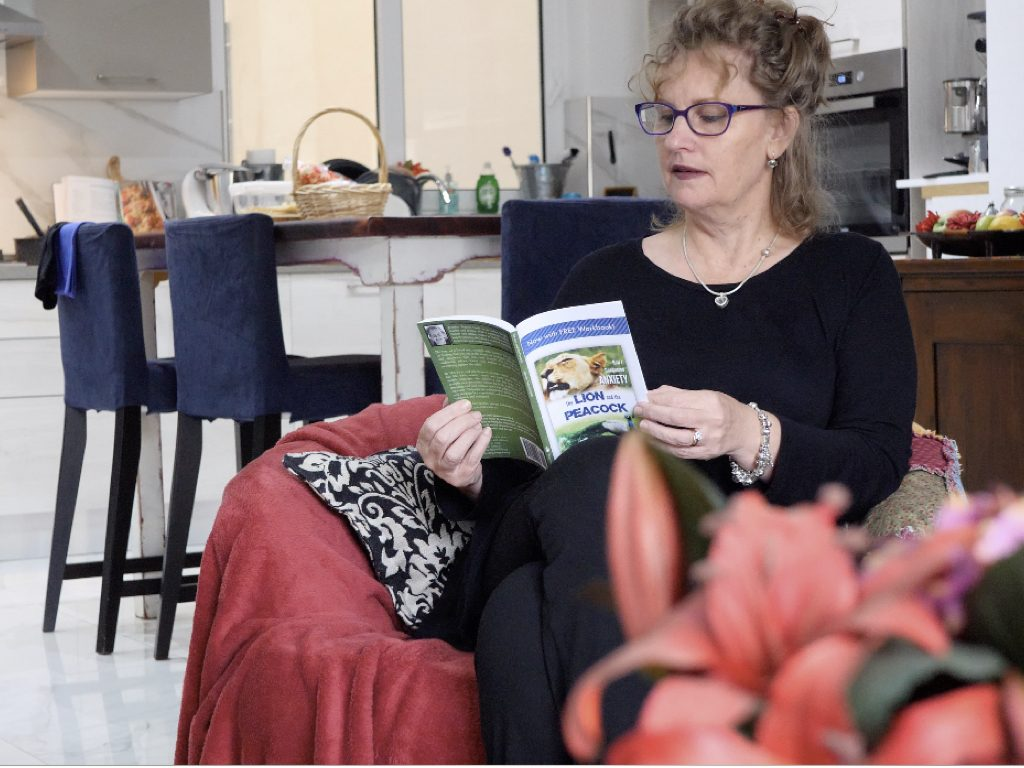 Wide-shot of a woman with curly, brown hair who wears violette glasses and is reading a book