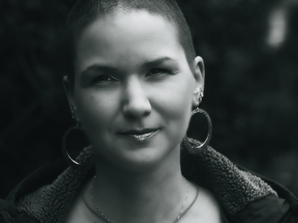 Black and white photo of Karina, a woman with 7 mm shaved hair and huge round earrings.