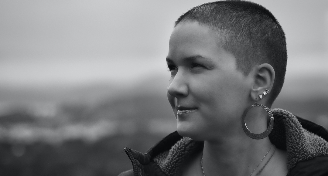 Black and white shot of Karina, a woman with super short brown hair and huge silver earrings